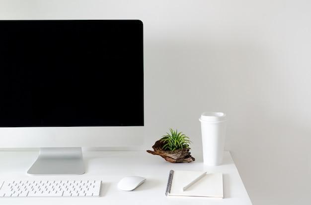 Tela de computador pessoal moderna na mesa branca com uma xícara de café.