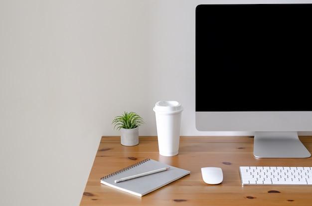 Tela de computador pessoal moderna na mesa de madeira com uma xícara de café.