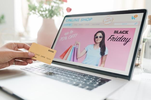 Tela de laptop com proteção de tela preta sexta-feira e mão feminina com cartão de crédito sobre teclado indo para fazer pedidos na loja online