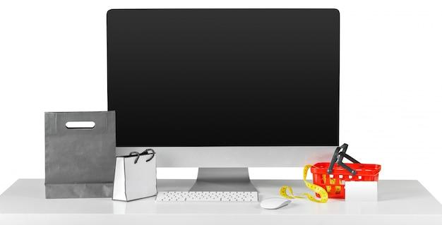 Tela de monitor de computador na mesa com acessórios de compras