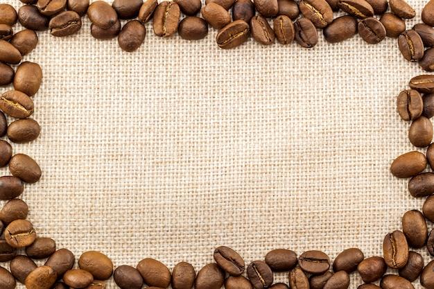 Tela de pano de saco de serapilheira e grãos de café colocados em volta