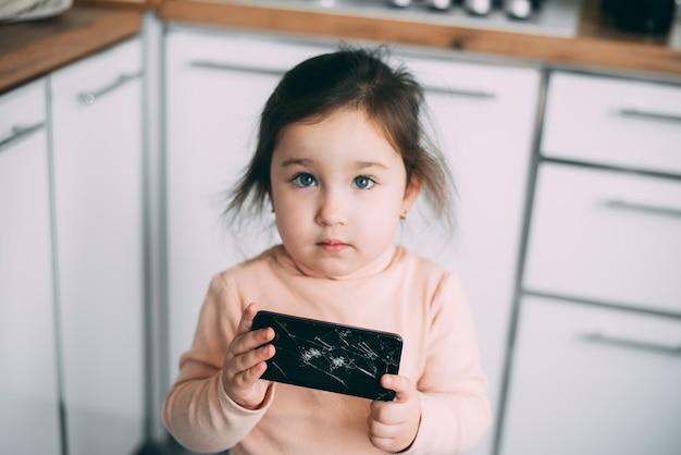 Tela de smartphone de vidro quebrado na mão de uma garota frustrada em casa na cozinha