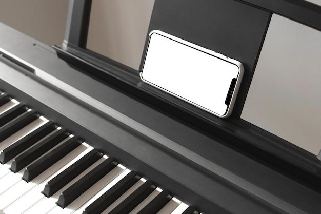 Tela de smartphone isolado nas mãos femininas perto do piano.
