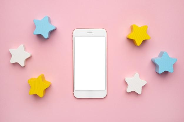 Tela do celular e brinquedo de desenvolvimento infantil para o desenvolvimento de habilidades motoras, um balanceador de estrelas de madeira em forma de lua crescente, em uma vista superior do fundo rosa