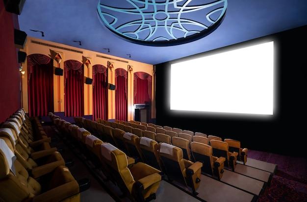 Tela do cinema em frente às fileiras de assentos no cinema mostrando uma tela branca projetada do cinematógrafo
