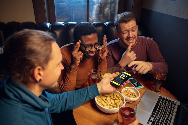 Tela do dispositivo com aplicativo móvel para apostas e pontuação. dispositivo com resultados da partida na tela, fãs animados no fundo durante a partida.