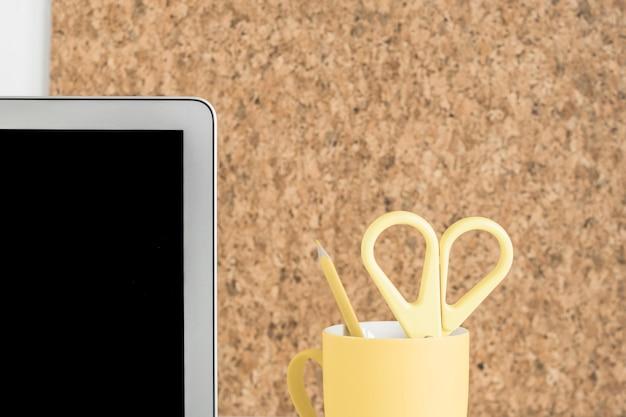 Tela do laptop com tesoura e lápis no porta-copos contra placa de cortiça