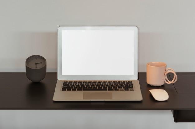 Tela do laptop em branco e uma xícara de café rosa