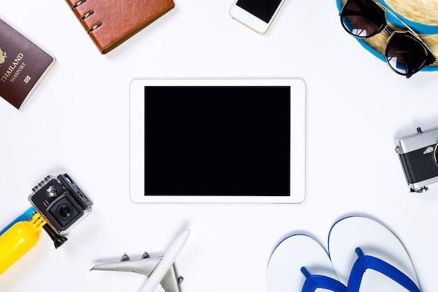 Tela do tablet em branco ao redor por objetos de viagem