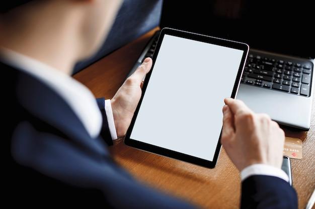 Tela do tablet usada por mãos masculinas sentadas em uma mesa.