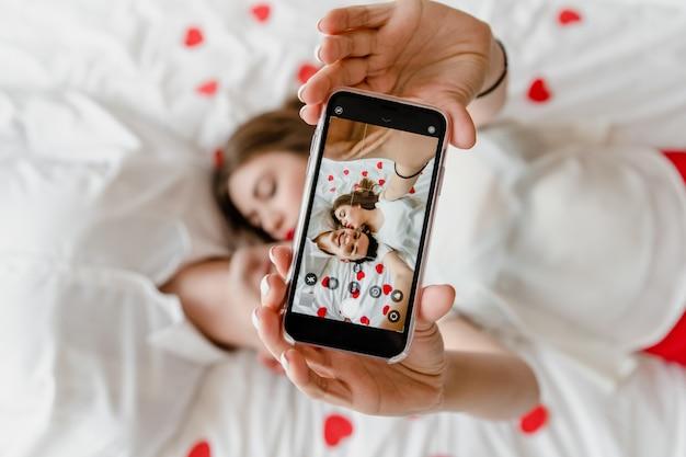 Tela do telefone com selfie de homem e mulher apaixonada na cama beijando