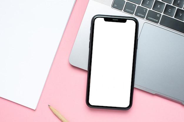 Tela do telefone móvel em branco, notebook e notebook de negócios na cor rosa com espaço de cópia