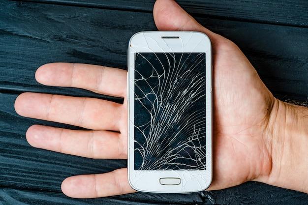 Tela do telefone quebrado na mão. vidro quebrado de smartphone
