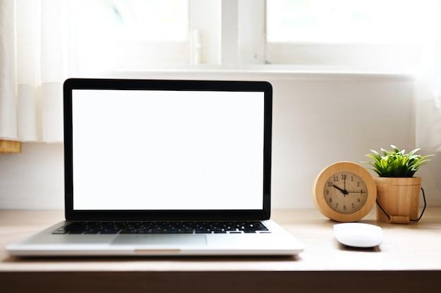 Tela em branco computador portátil moderno na mesa de madeira em fundos de exibição de escritório em casa