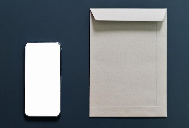 Tela em branco da maquete de smartphone com envelope marrom em preto