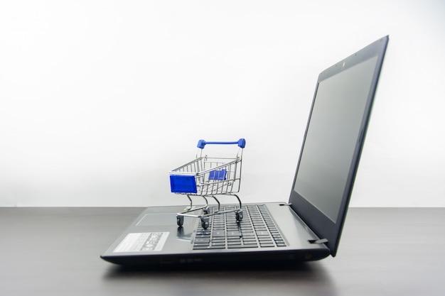 Tela em branco do computador notebook com carrinho de compras na mesa de madeira