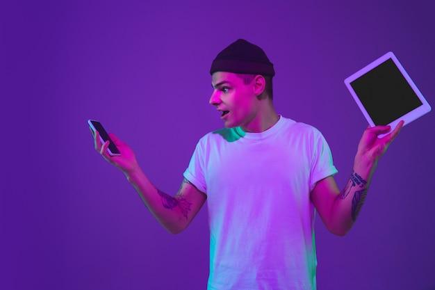 Tela em branco do dispositivo. retrato do homem caucasiano isolado no fundo roxo do estúdio em luz de néon rosa. lindo modelo masculino no casual. conceito de emoções humanas, expressão facial, vendas, anúncio.