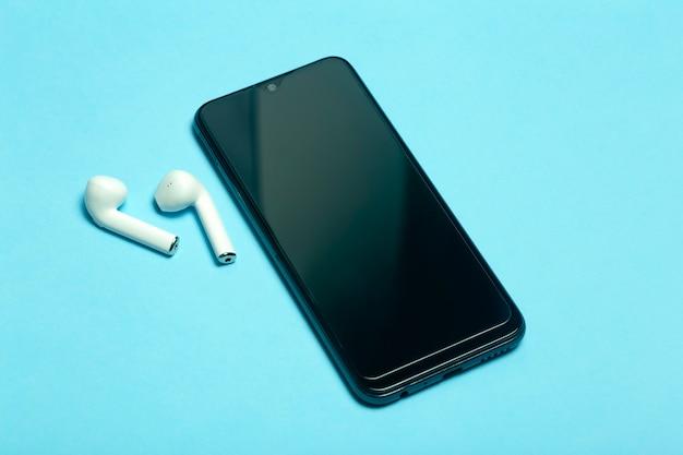 Tela em branco do smartphone em um fundo colorido com fones de ouvido.