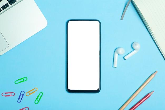 Tela em branco do smartphone em um fundo de lugar de mesa de trabalho com fones de ouvido.