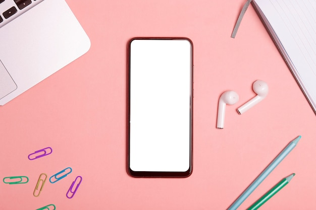 Tela em branco do smartphone em uma mesa de trabalho com fones de ouvido.