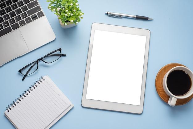Tela em branco do tablet do espaço de trabalho e equipamentos de trabalho