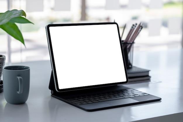 Tela em branco do tablet e uma xícara de café em branco na mesa do escritório