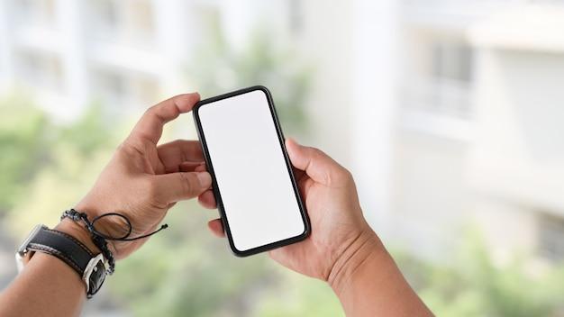 Tela em branco do telefone inteligente móvel na mão do homem