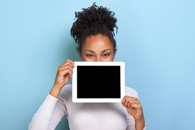 Tela em branco vazia preta do ipad na mão feminina, a espreitar por trás da tabuleta