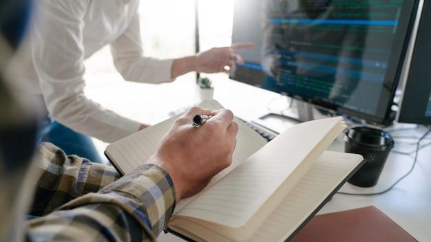 Tela inicial para jovens desenvolvedores programadores sentados em mesas trabalhando em computadores para desenvolver programação e codificação para encontrar a solução para o problema no novo aplicativo