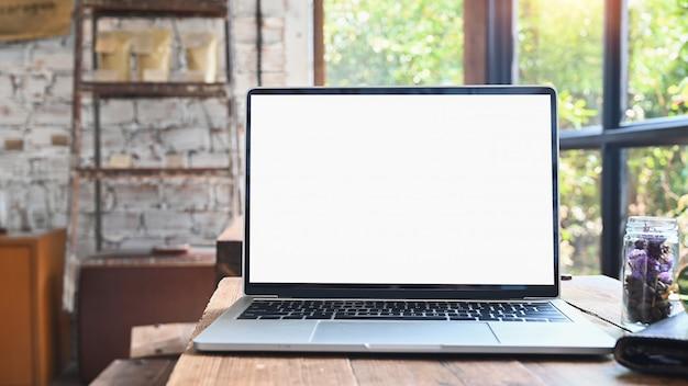 Tela isolada do computador portátil do modelo na tabela de madeira no café.