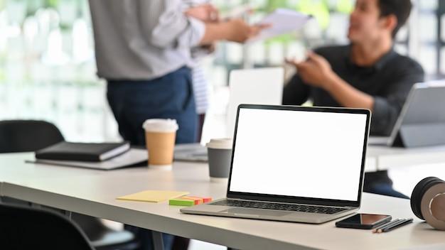 Tela isolada do laptop na mesa de reunião criativa.