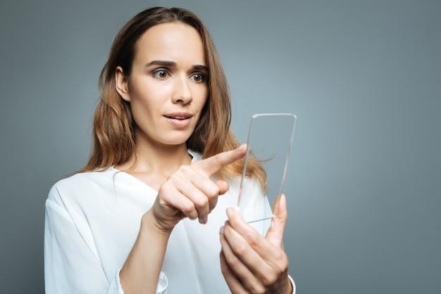 Tela sensorial. mulher jovem e agradável segurando seu smartphone e apontando para ele enquanto usa tecnologia moderna
