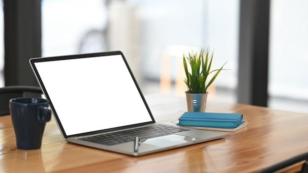 Tela vazia do computador portátil de maquete na mesa de madeira.