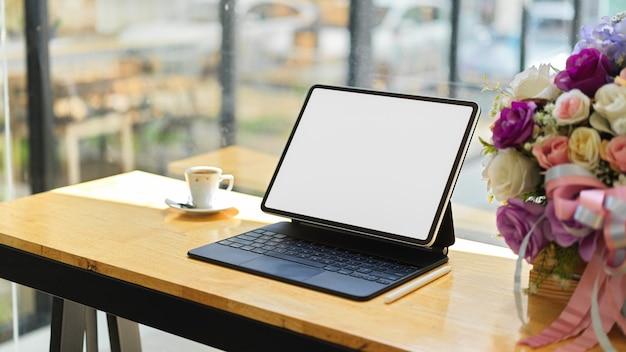 Tela vazia do tablet portátil simulada com xícara de café e vaso de flores na mesa de madeira da cafeteria