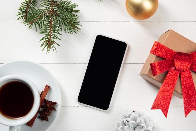 Tela vazia em branco do smartphone na parede de madeira branca com decoração colorida do feriado e presentes.