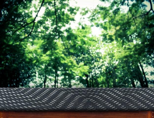 Tela vazia tábua de mesa em grupo borrado de árvores, modelo mapeado para exibição do seu produto, apresentação de negócios
