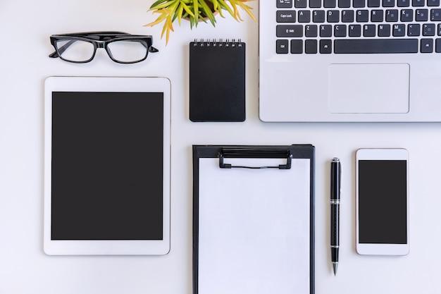 Tela vazia, telefone inteligente e tablet com laptop no escritório de mesa de negócios com espaço de cópia, vista superior