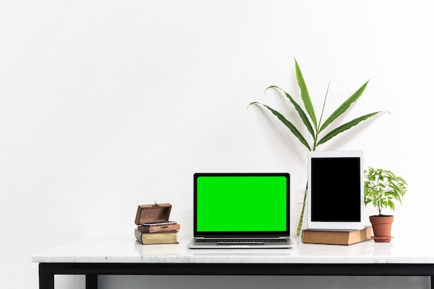 Tela verde do laptop e tablet tela preta na mesa de mármore