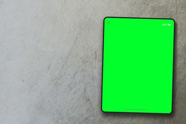 Tela verde do tablet em fundo de cimento. vista do topo. chave de croma.