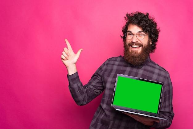 Tela verde em branco no laptop, homem feliz com barba, sorrindo, apontando para longe e segurando o laptop