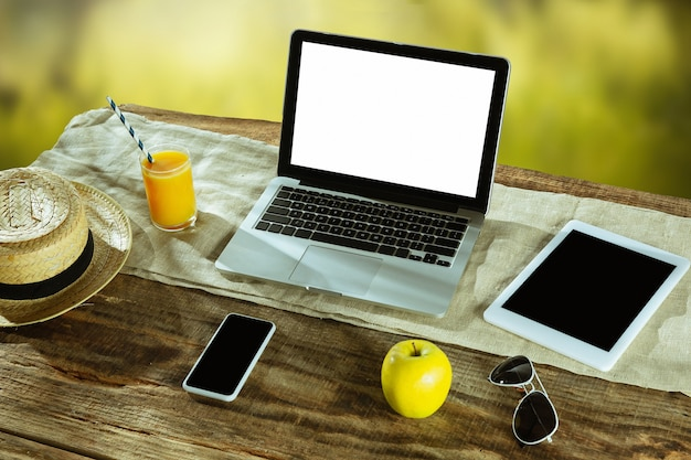 Telas em branco de laptop e smartphone em uma mesa de madeira ao ar livre com a natureza na parede, simulação acima.