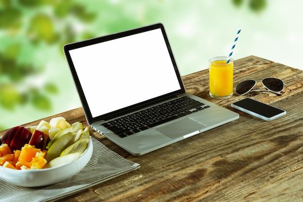 Telas em branco de laptop e smartphone na mesa de madeira ao ar livre com a natureza