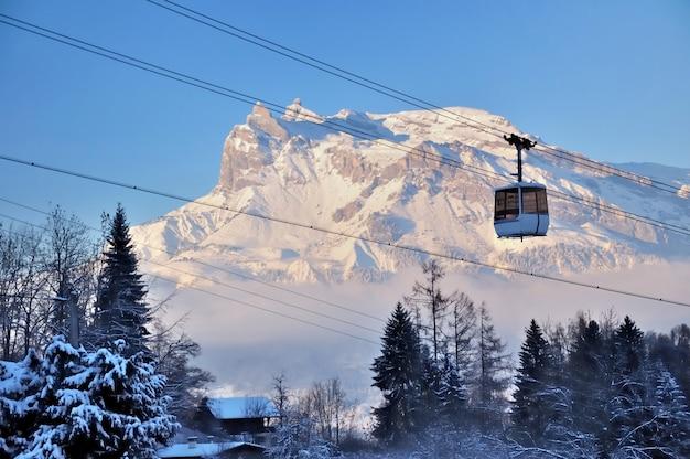 Teleférico acima das árvores e na frente da montanha de pico nevado