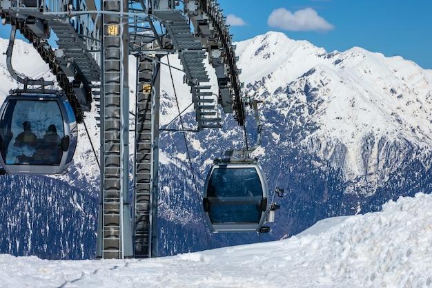 Teleférico com assentos sobre a montanha e caminhos de céus e pranchas de snowboard