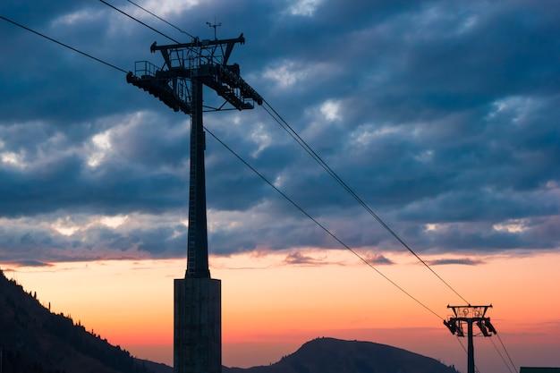 Teleférico da montanha no fundo do sol.