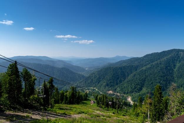 Teleférico de cadeira nas montanhas. escalar a montanha em um elevador. bela vista do topo da montanha às colinas cobertas por floresta de coníferas.