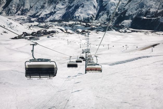 Teleférico e pista de esqui de neve em um dia ensolarado na montanha. montanhas do cáucaso, geórgia, região de gudauri