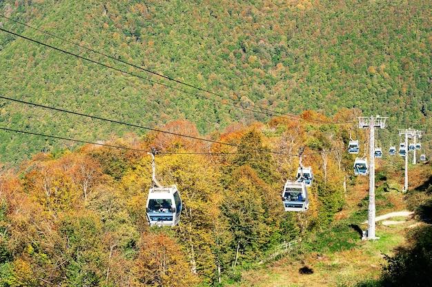 Teleférico em montanhas com árvores outonais