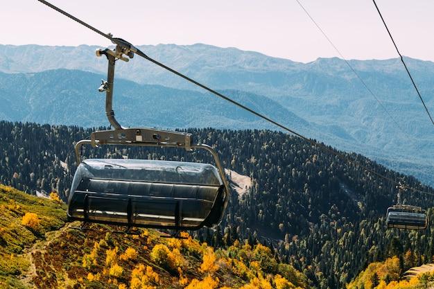 Teleférico nas montanhas acima da floresta de outono