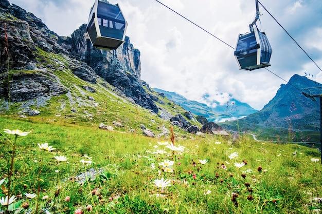 Teleférico passando por um prado alpino
